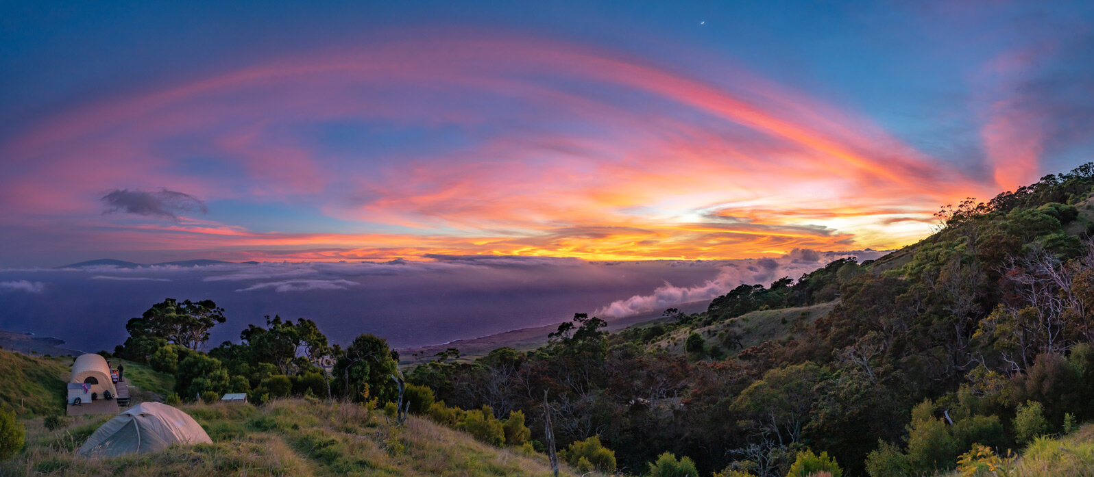 A panoramic perspective of a breathtaking sunset from camp. On the right, native forest blankets the gulch under a rising crescent moon, while the distant peaks of the Big Island emerge from the Pacific at left.