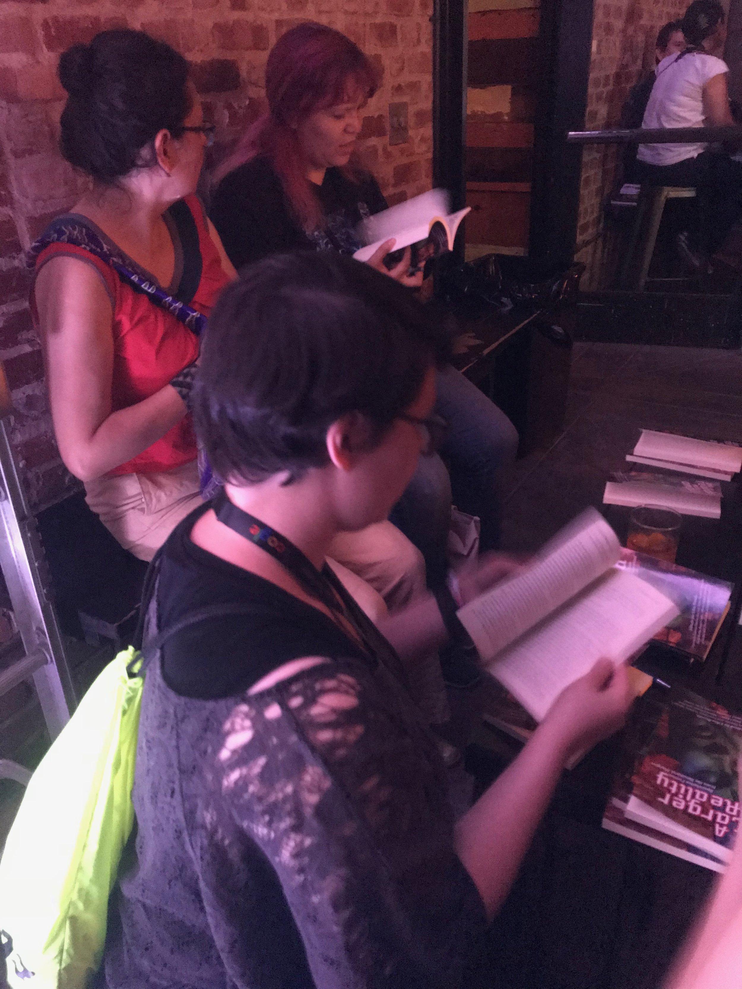 Angela Lujan, Libia Brenda, and Raquel Castro signing books