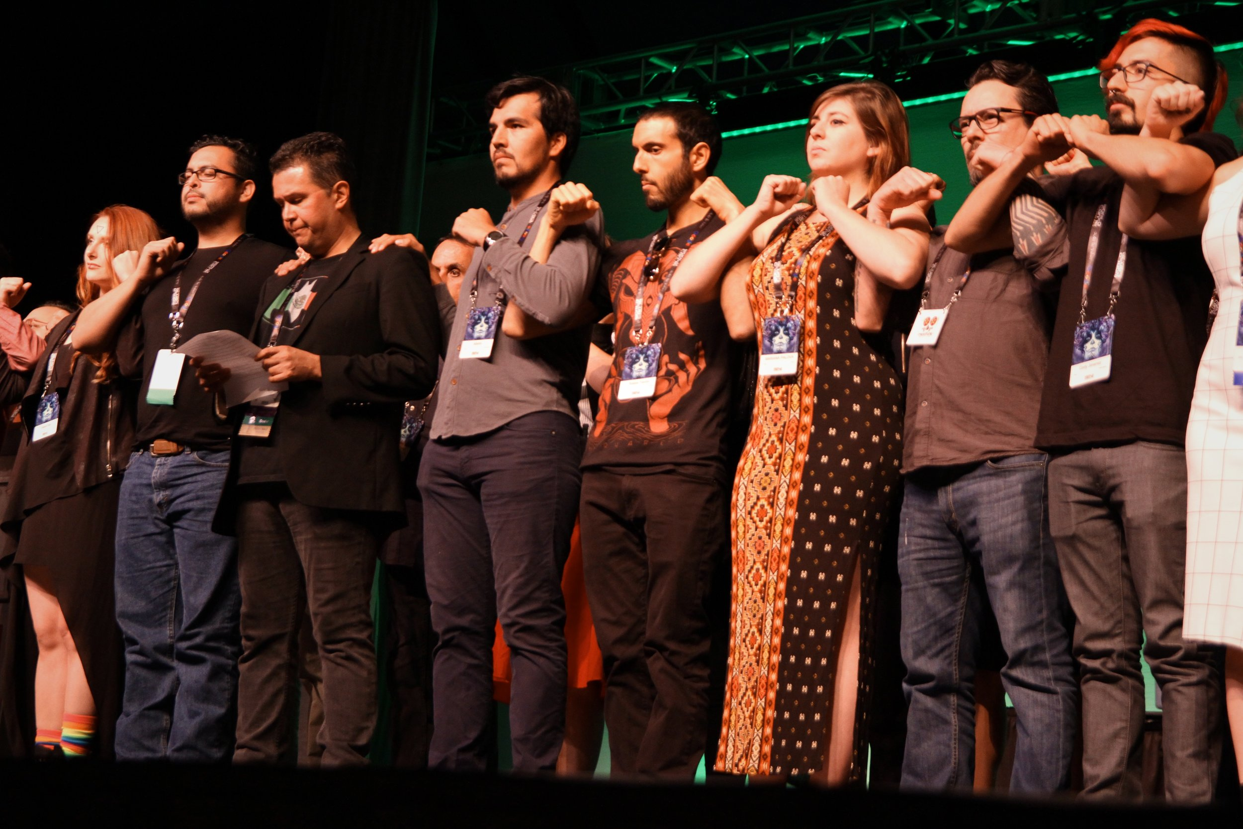 Mexicanx Initiative Participants standing in solidarity as John Picacio reads Lauren Snow's manifesto at Worldcon 76's opening ceremonies (Copyright 2018 Richard Canfield)