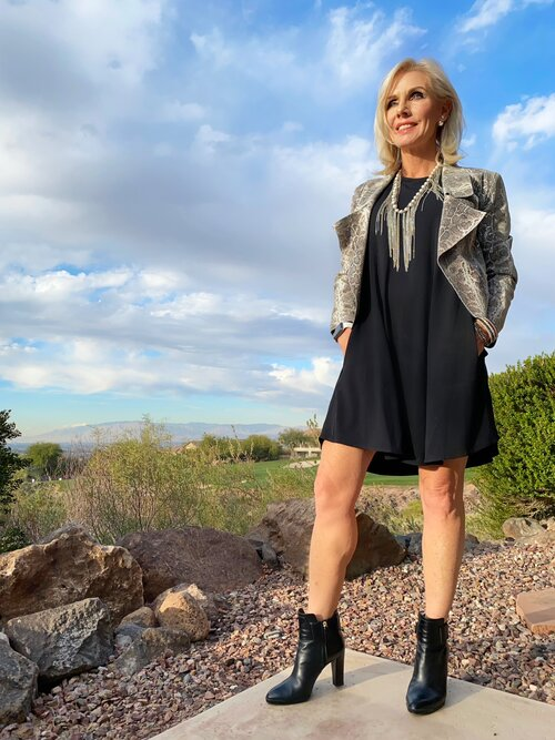 Liz is wearing SheBird's  Tunic Tank Dress  in Jet Black, paired with a moto jacket, booties, and a statement necklace.