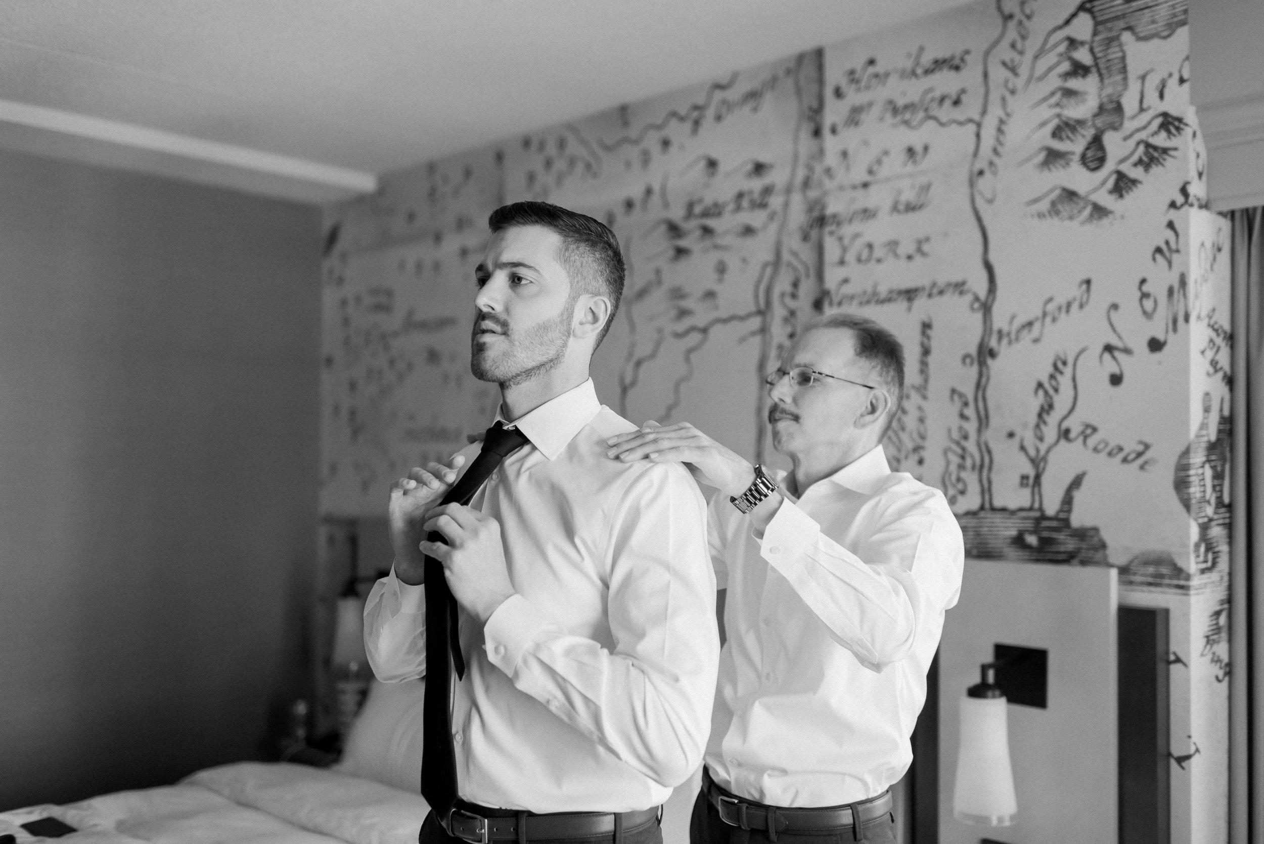 groom tying tie_CT wedding photographer_lace factory