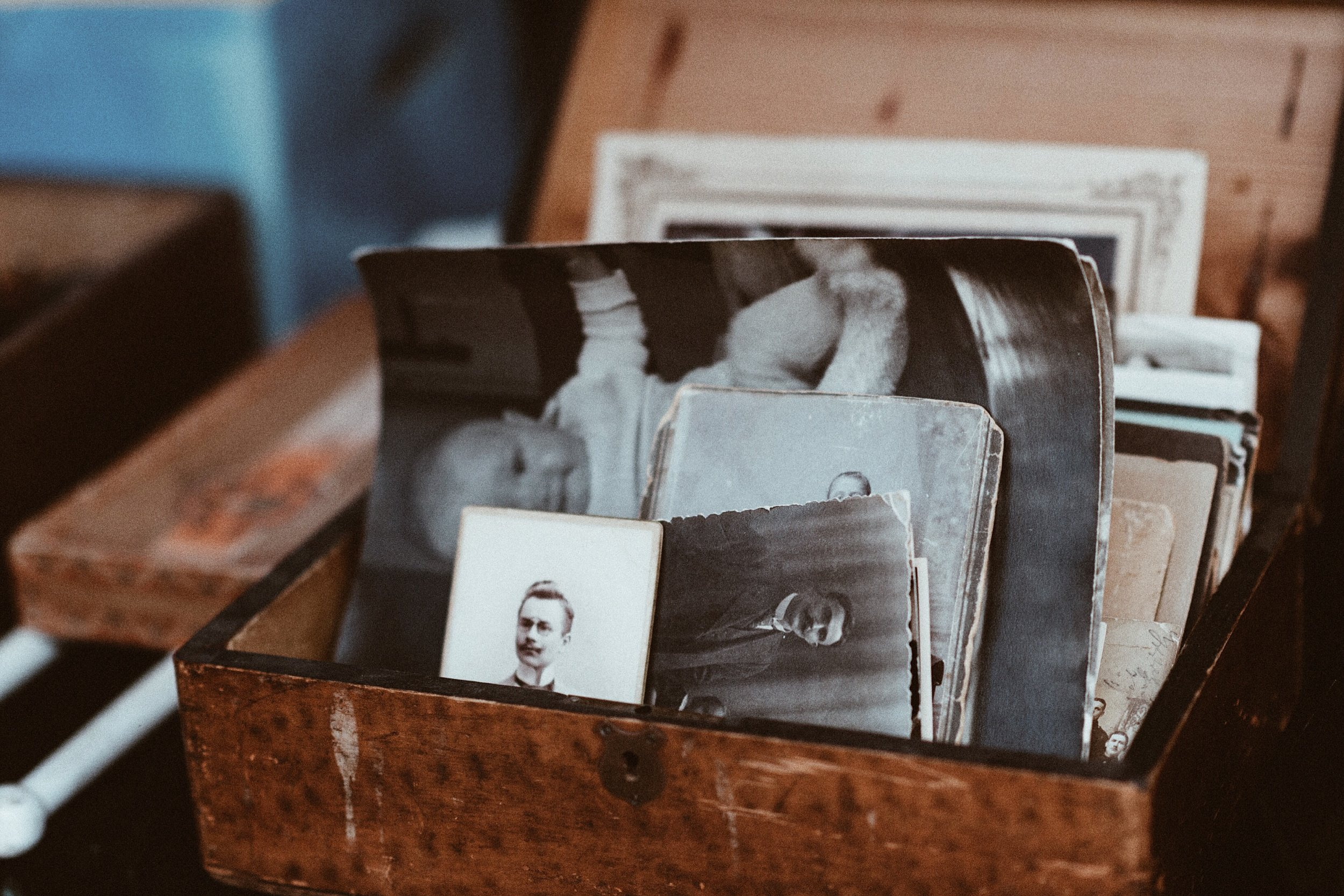 Image is of old black and white photographs in a worn wooden box, presumably the photographer's family members from earlier times.