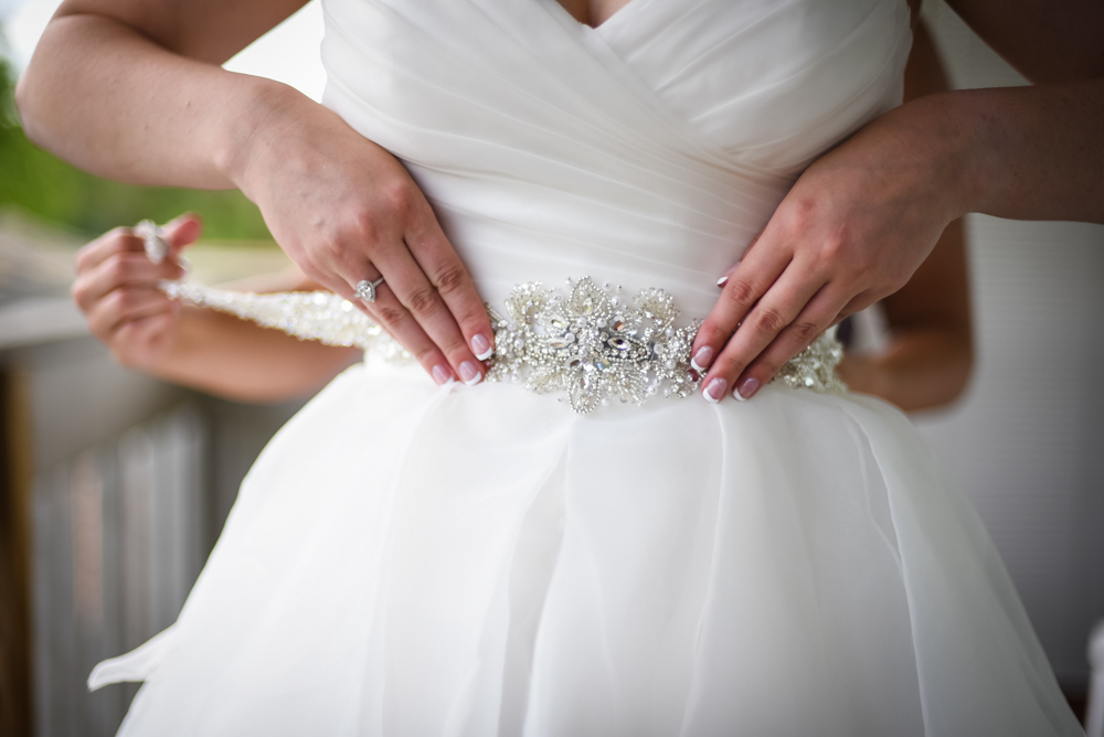 bride putting crystal sash on wedding dress