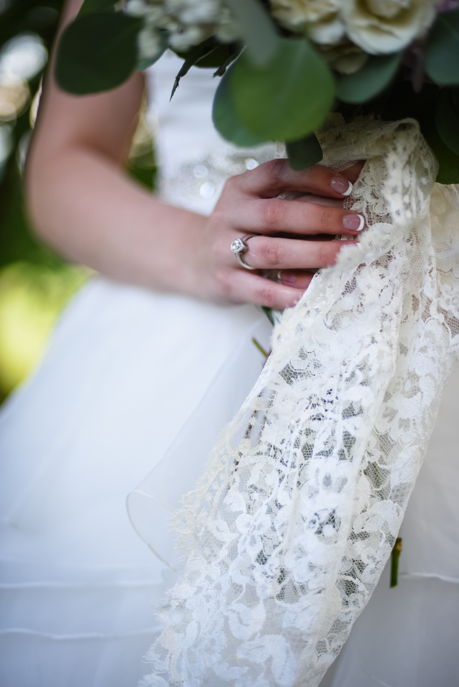 detail wedding photography bride holding wedding bouquet with lace