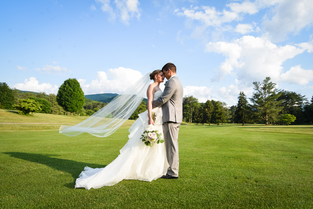 bride and groom facing each other photographed on golf course