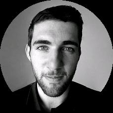 Zwart-wit foto van man in zijn late 20s met blik gericht op de camera in zwart hemd.