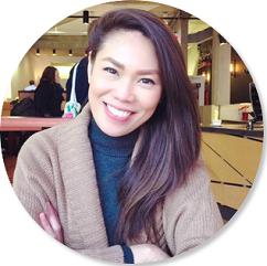 Vrouw met bruin haar zit met de handen gevouwd in een bruine sweater en donkerblauwe turtleneck in een café.
