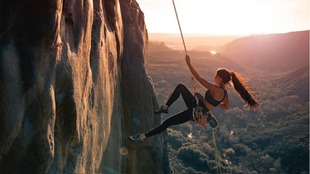Jonge vrouw beklimt in sportieve outfit een rots en heeft een touw vast in haar handen met een zonsondergang en bomen op de achtergrond en ondergrond.
