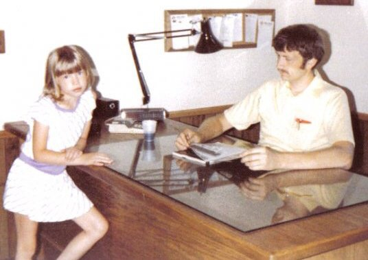 6-year old Jamie with her dad at his office in Leland, Iowa