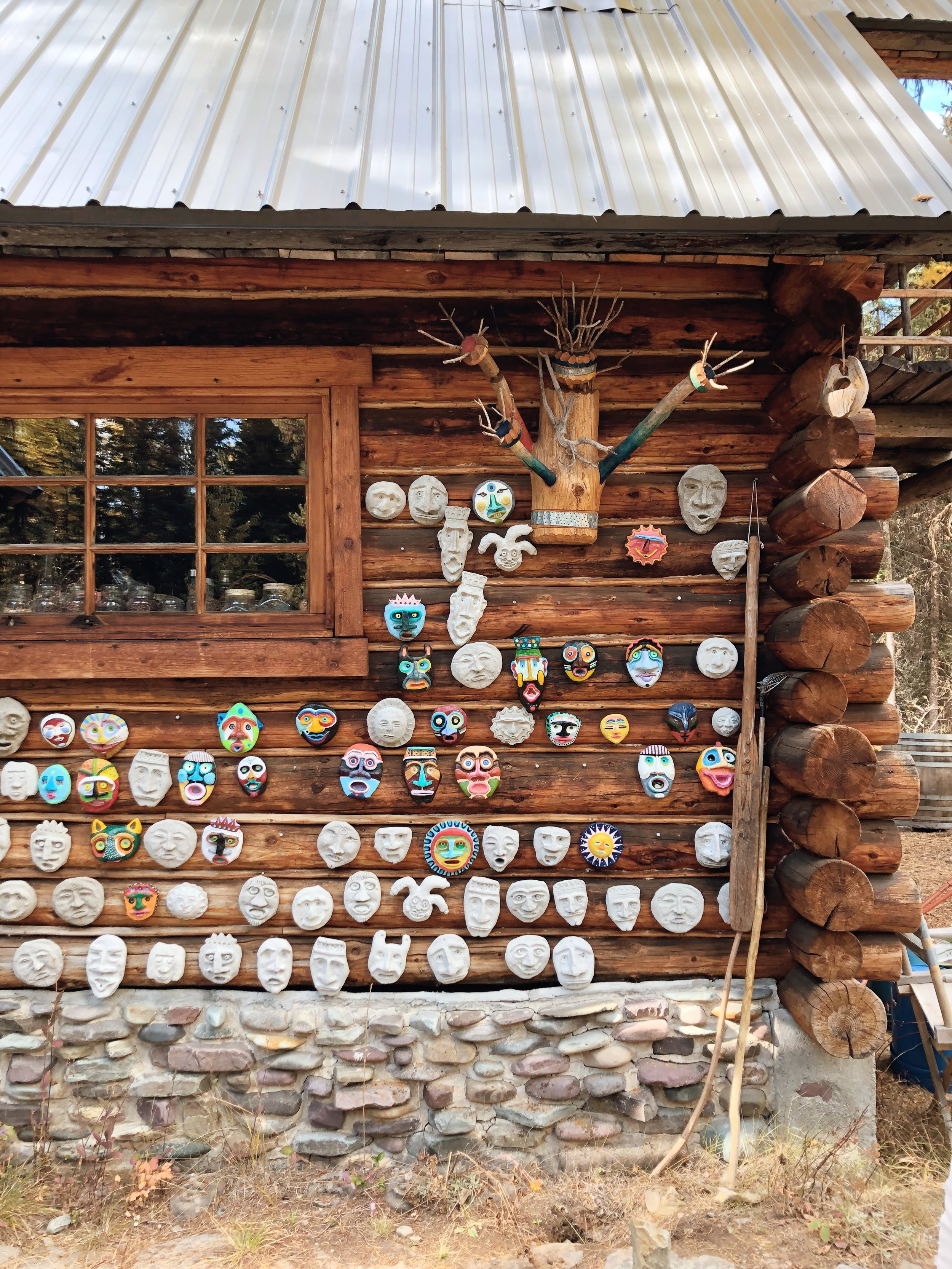 Painted clay masks, made by Peter, are nailed to the log exterior of his home, studio, and gallery.