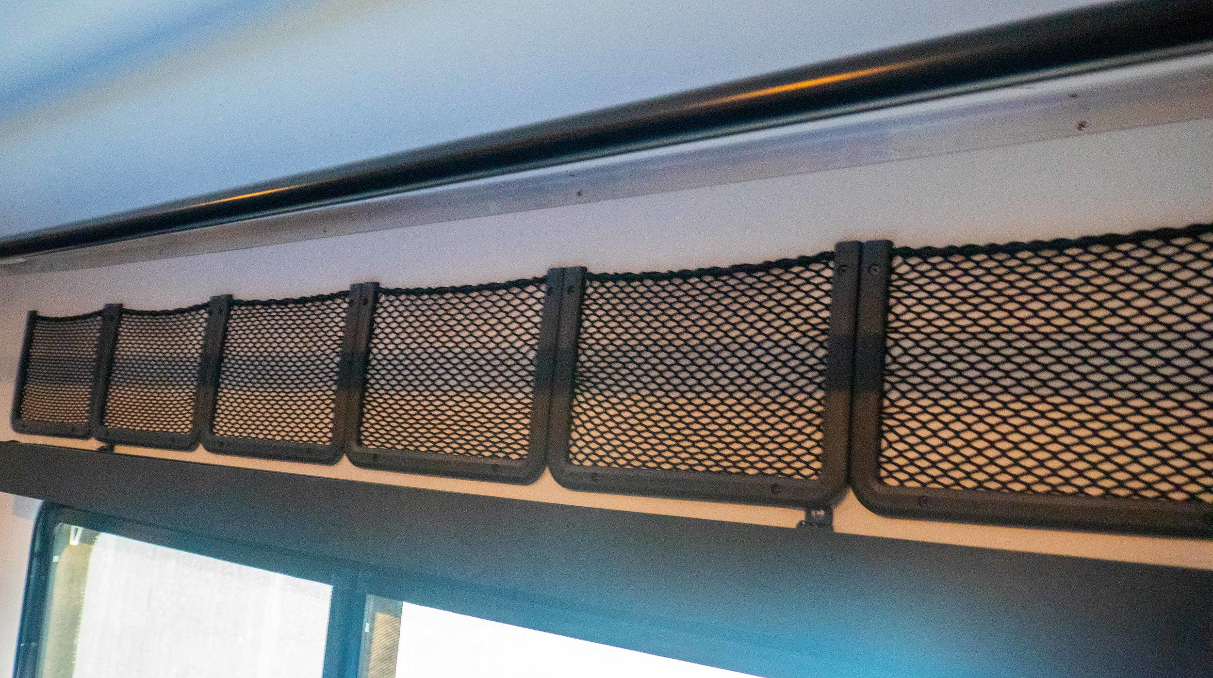 extensive mounted storage netting above bed