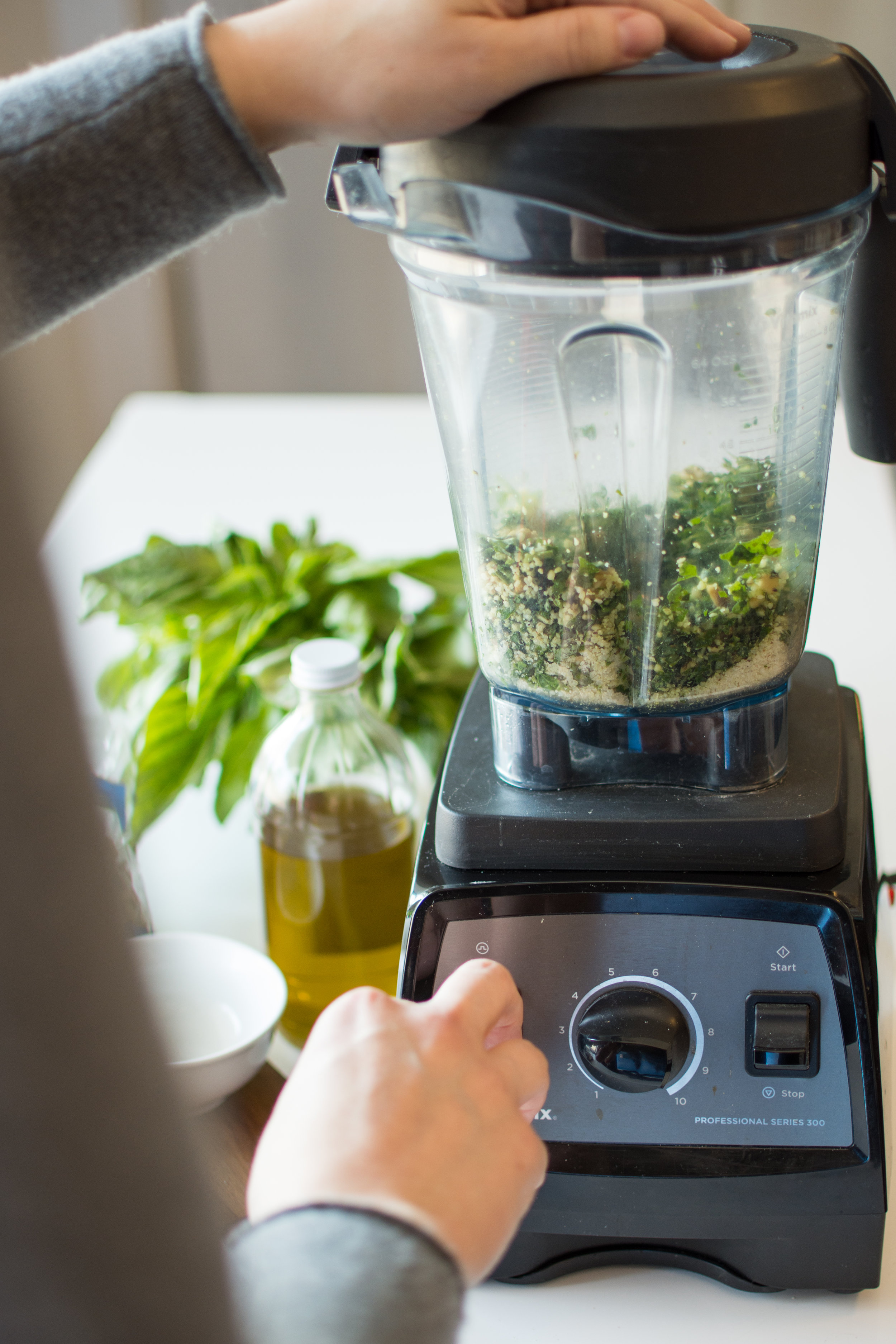 Process all ingredients until mixture resembles a paste, about 1 minute, scraping down the sides of your blender if needed. With the processor running, slowly pour the 2/3 olive oil through the feed tube and process until the pesto is thoroughly blended.