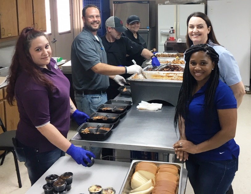 BRECO employees Hailey Kimble and Derek Veade serve lunch to DEMCO employees for National Lineman Appreciation Day.