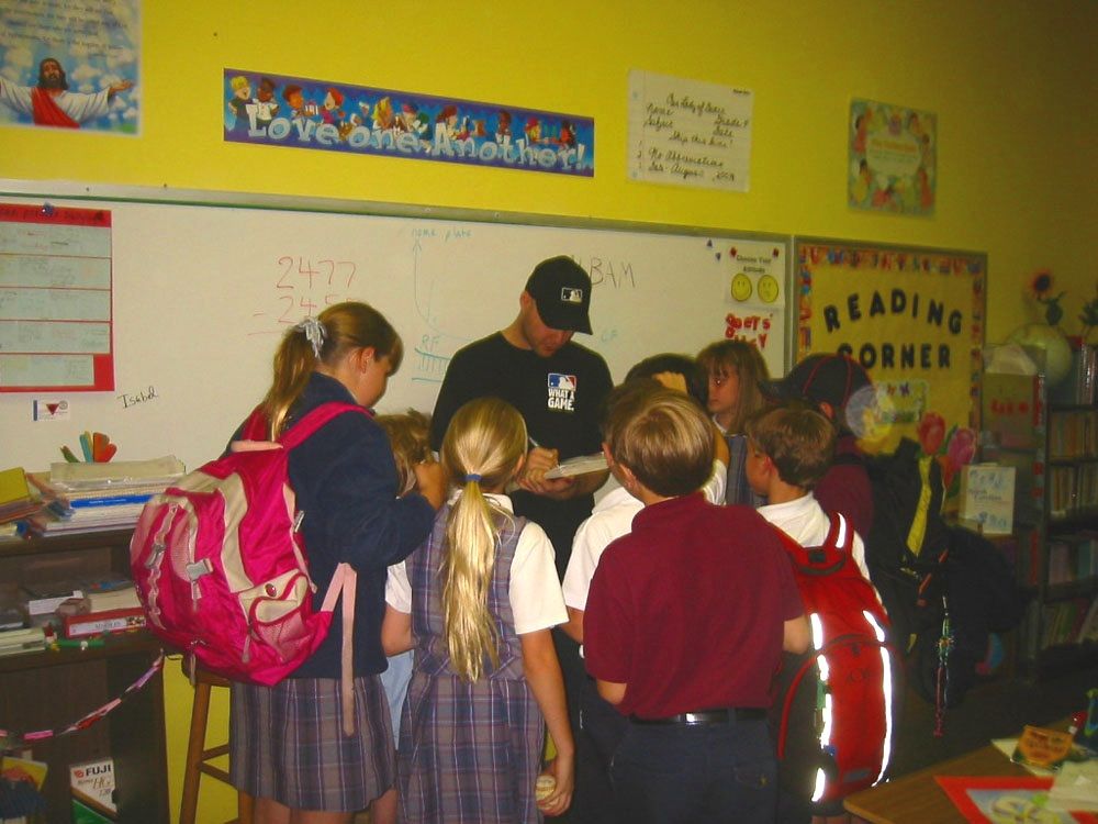 signing autographs after talking baseball with a group of 4th graders