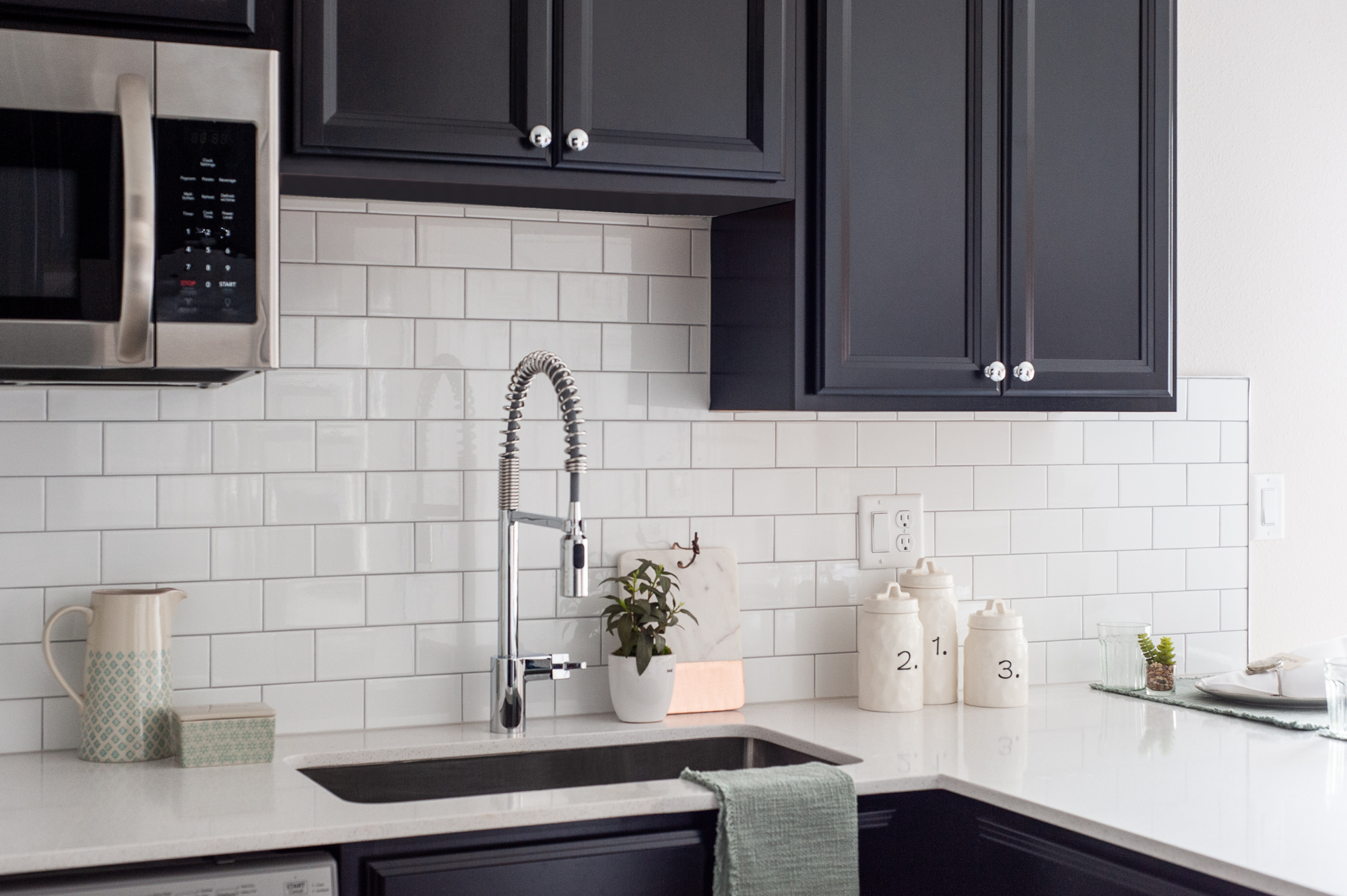 Micamy Design Studio_Model Home_Interior Design_Orchard Cove_Modern Coastal_Guest Suite_Kitchenette_Next Generation Suite_Small Kitchen_Dark Cabinets_White Subway.jpg