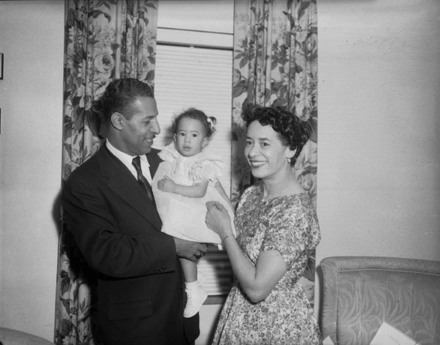 Charlene Foggie-Barnett pictured with her parents in their Ewart Drive living room. Photo by Teenie Harris, 1959.