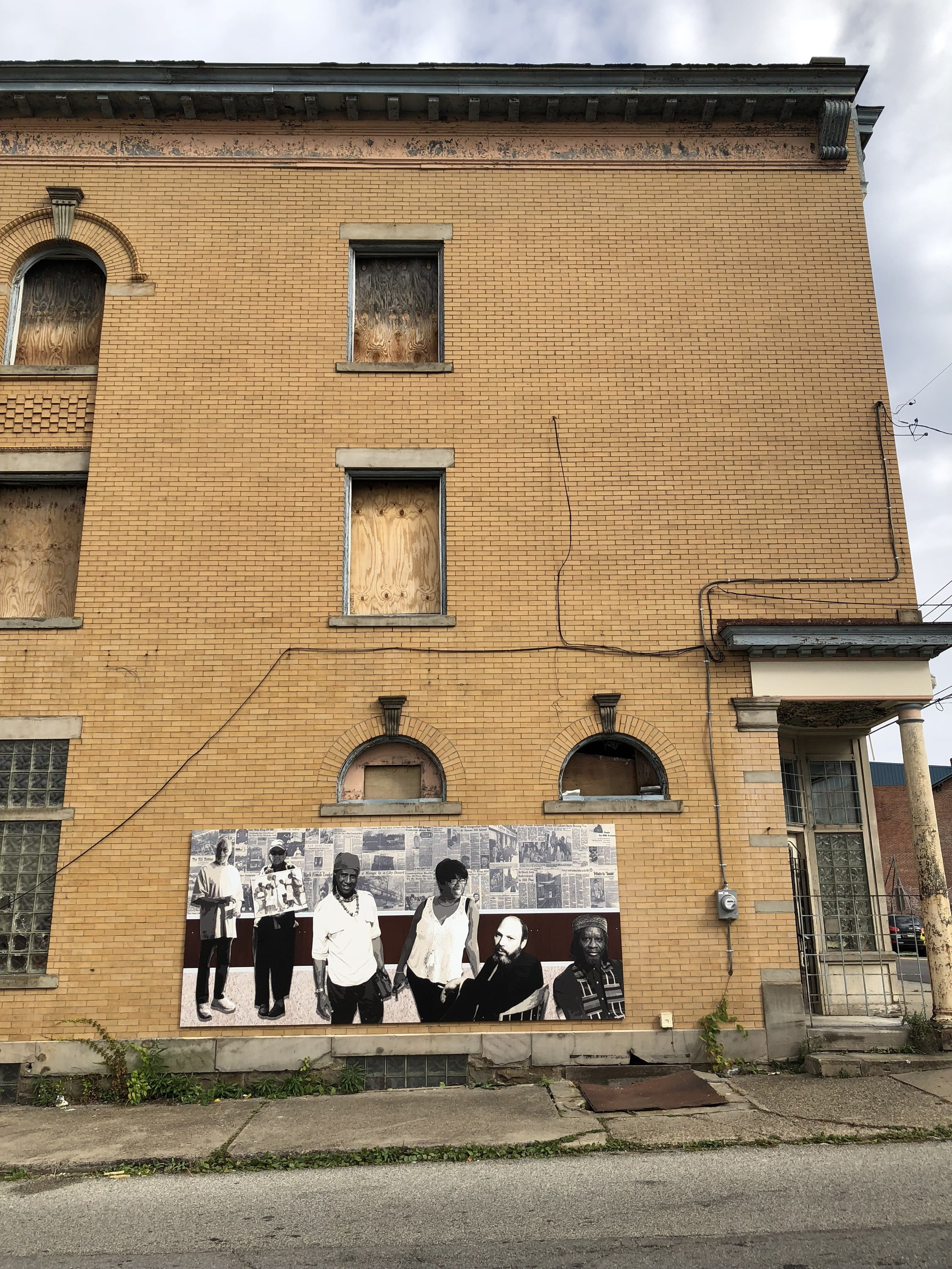 """""""The Beat Keepers"""" installation on the side of the former """"Doc's New Ideas"""" building, recognizing Hill District artists past and present. Centre Avenue, 2018."""