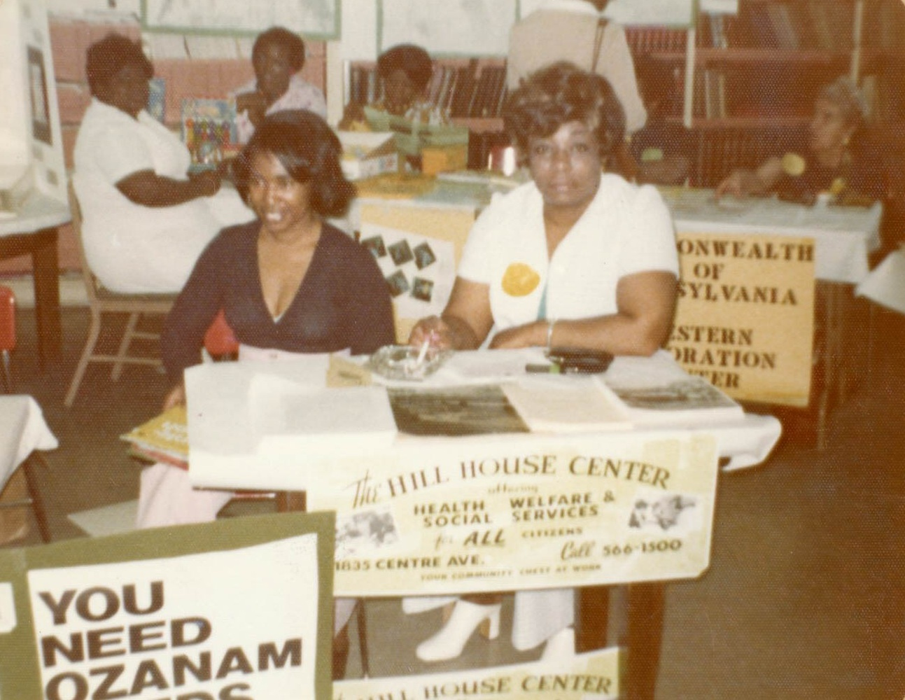 Two women table for the services available to all citizens and Hill residents through the Hill House Center at the Wylie Avenue Library c. 1974. Courtesy Carnegie Library - Hill District Branch.