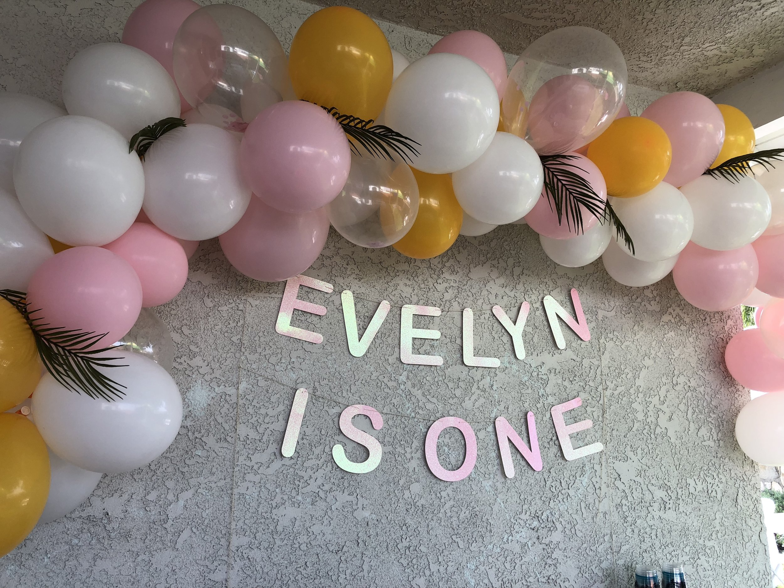DIY balloon arch with leaves and name sign.JPG