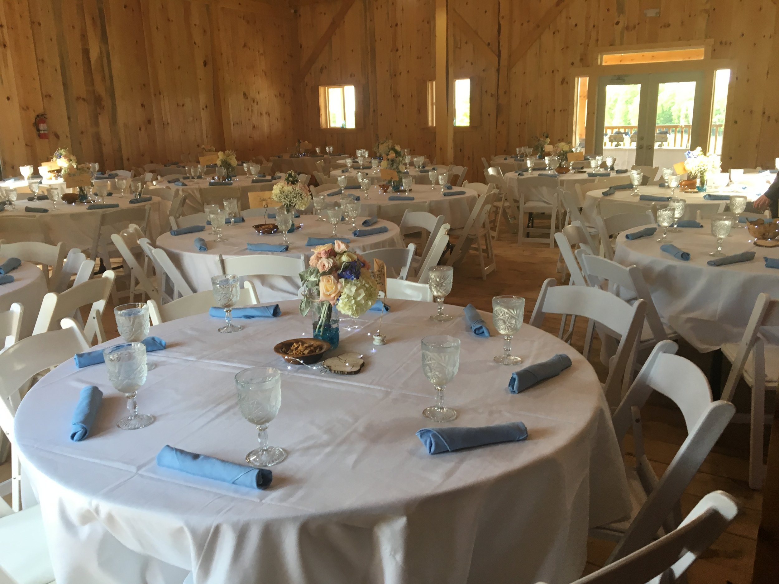 Guest tables set with linens, blue napkin rolled silverware and water goblets.