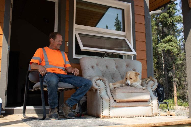 Cory Thompson and his a three-legged Australian Shepherd mix Kyla sit outside his tiny home in Carcross, Yukon. [Photo © Raisa Patel]
