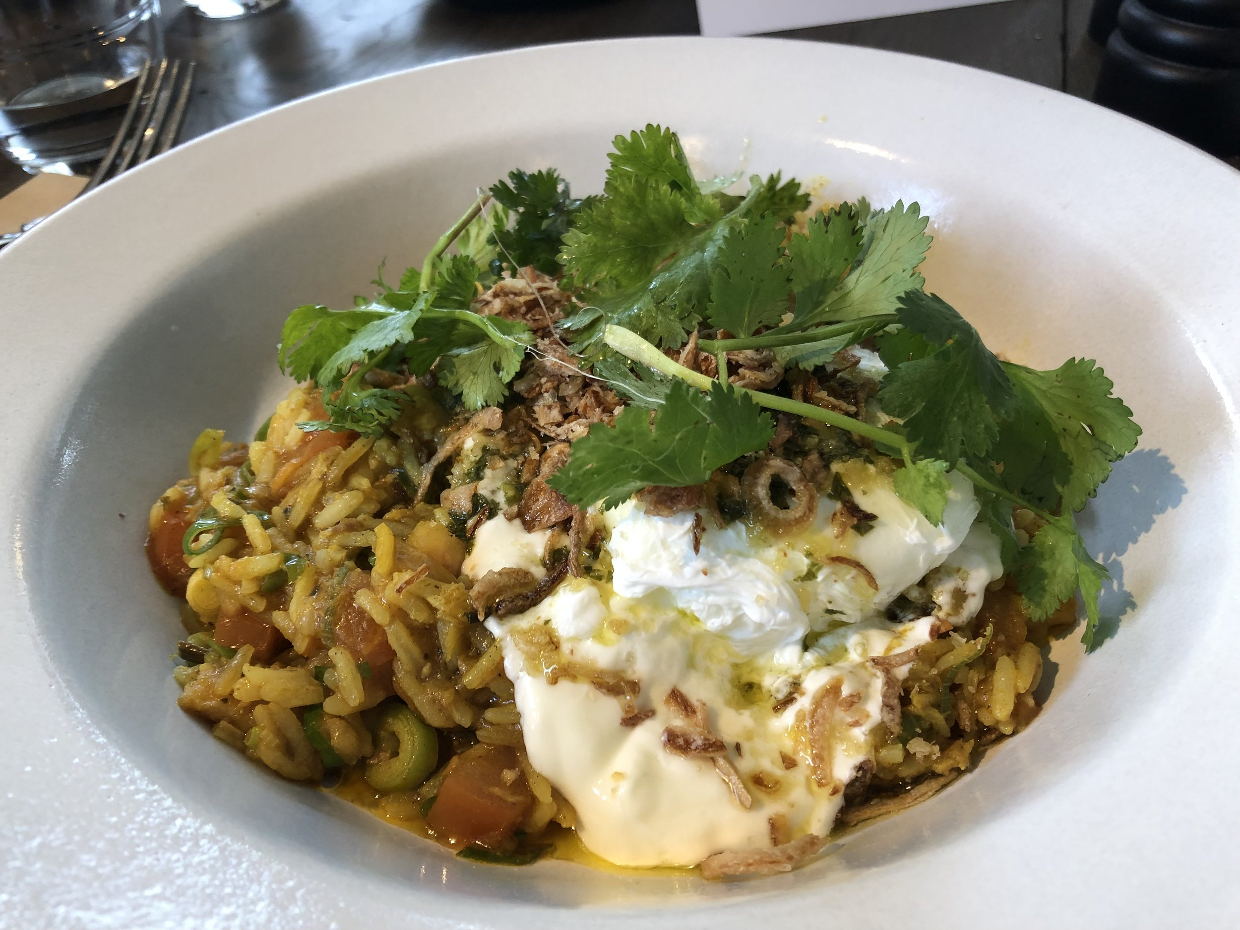 Smoked fish kedgeree with poached egg, fried shallots, labneh and chimichurri