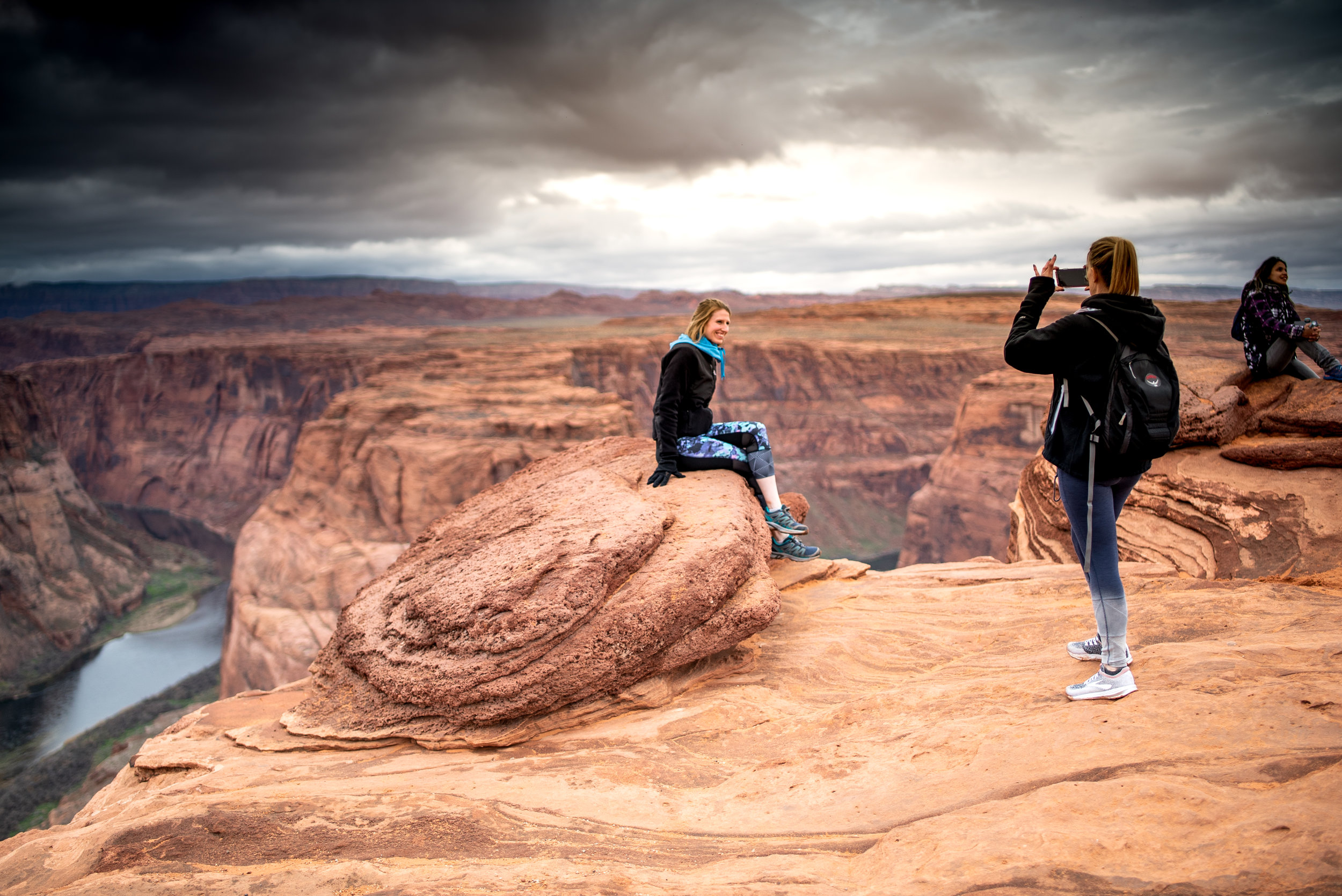 Friends take photos of each-other near the edge of the 1,000ft cliff that drops to the Colorado River.