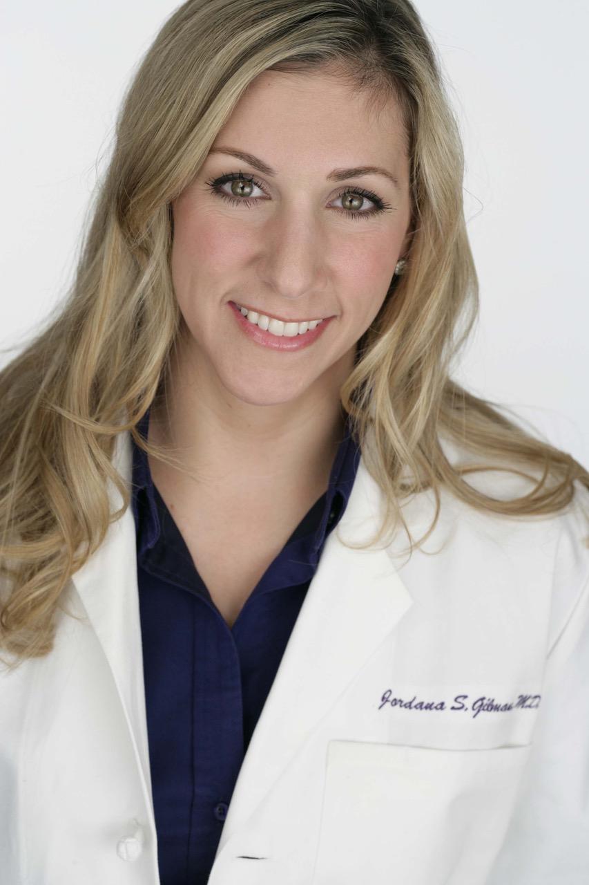 Dr. Gilman dermatologist white coat smiling