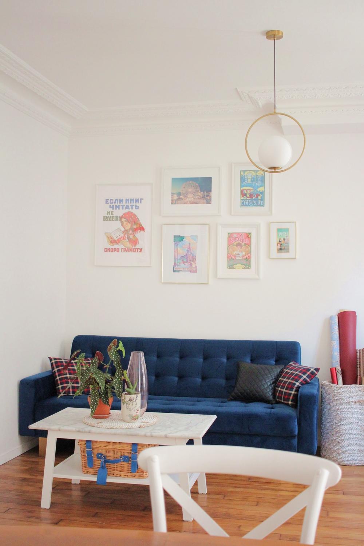 Décoration appartement parisien canapé velours bleu mur photos table marbre