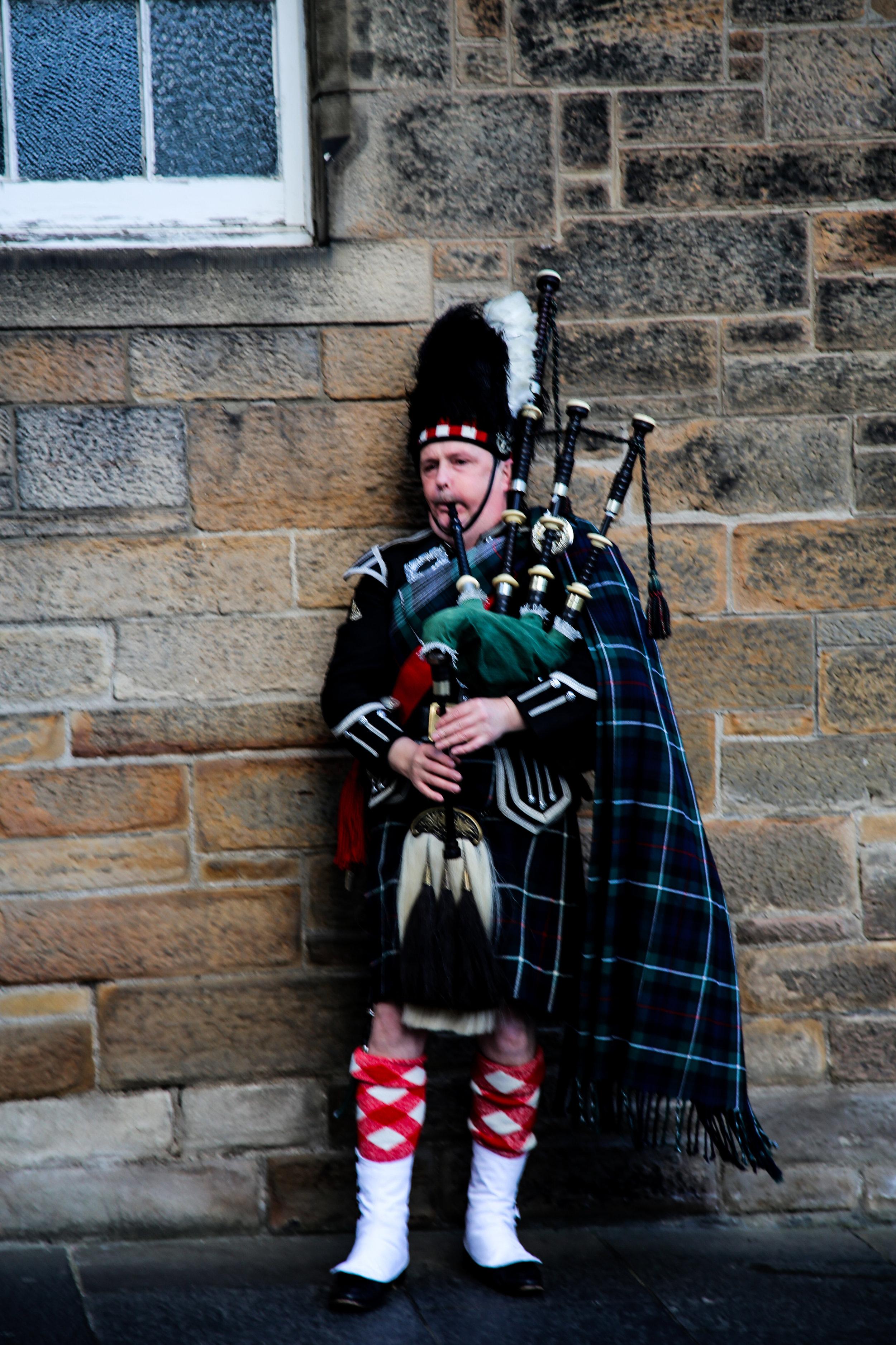 Scottish highlander playing bagpipes Edinburgh