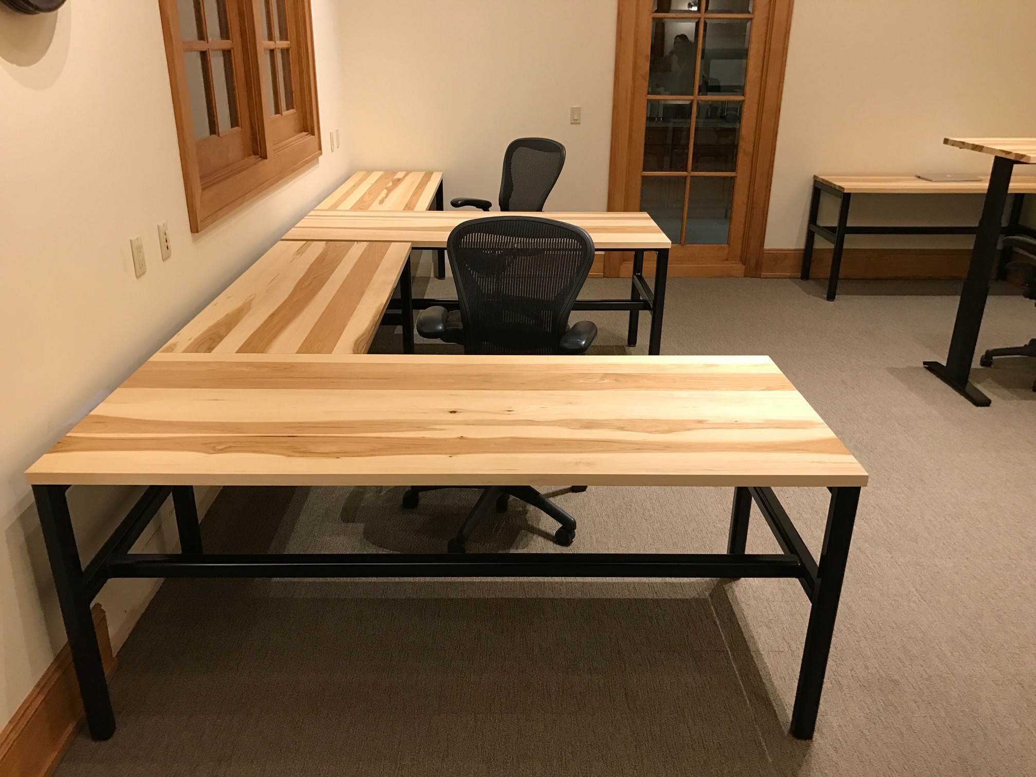 Solid Wood Tables with Style - When a local ice cream company contacted us looking to add character to their office space, solid wood desks immediately came to mind. Mounted on black powder-coated steel frames or electric height-adjustable legs, the hickory tables accented the space beautifully and created a look as unique as the flavors they produce.