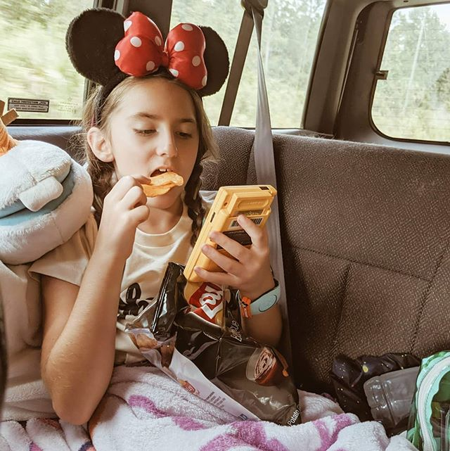 Heading to magic kingdom today! This is how Madi travels on the 2 hour trip! A bag of BBQ chips and Dad's old Gameboy color!