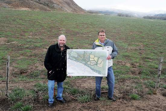 Kristin Anderson/kanderson@vaildaily.com Haymeadow developer and Eagle resident, Ric Newman, and land planner, Rick Pylman, display the recently submitted Haymeadow plan at a location on the western boundary of the property.