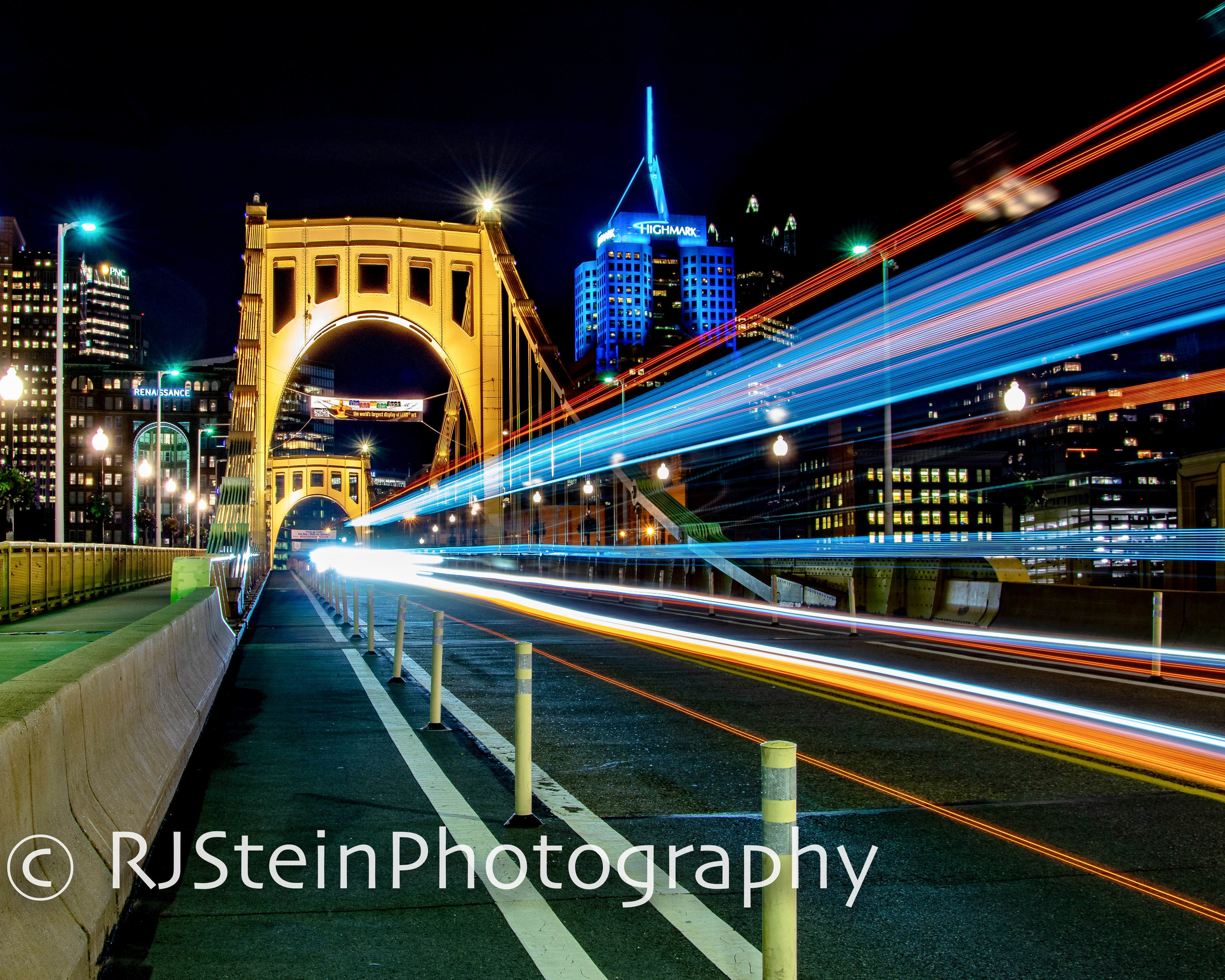 Pittsburgh's skyline is lit up by a passing bus on the Roberto Clemente Bridge.