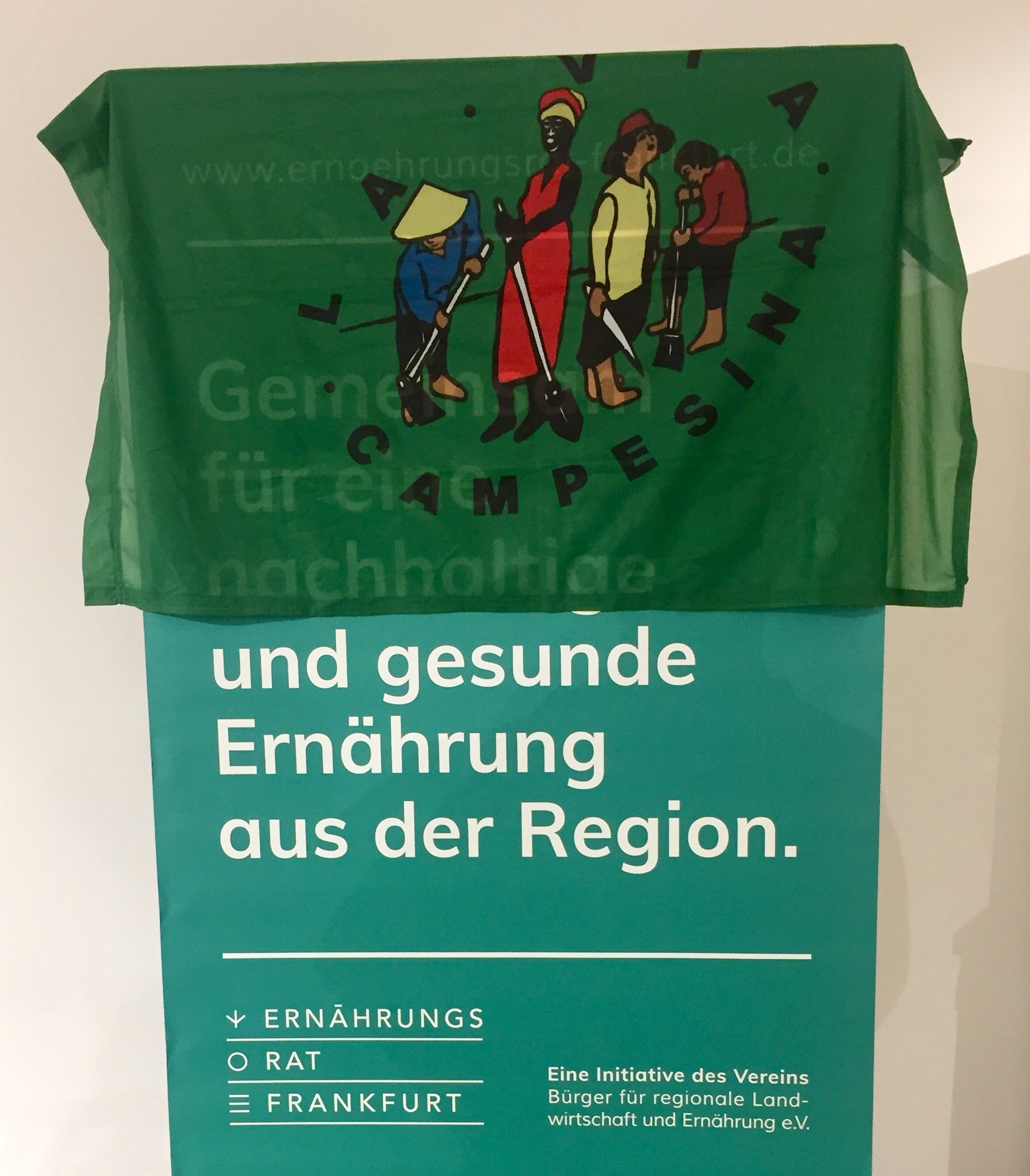 Nik Hampel, who together with his wife runs a family-owned beef farm in Vogelsburg just outside of Frankfurt, showed solidarity with the Food Sovereignty movement by draping the  La Via Campesina  flag over this Frankfurt Food Policy Council poster as he took the stage Friday evening for an open panel discussion.