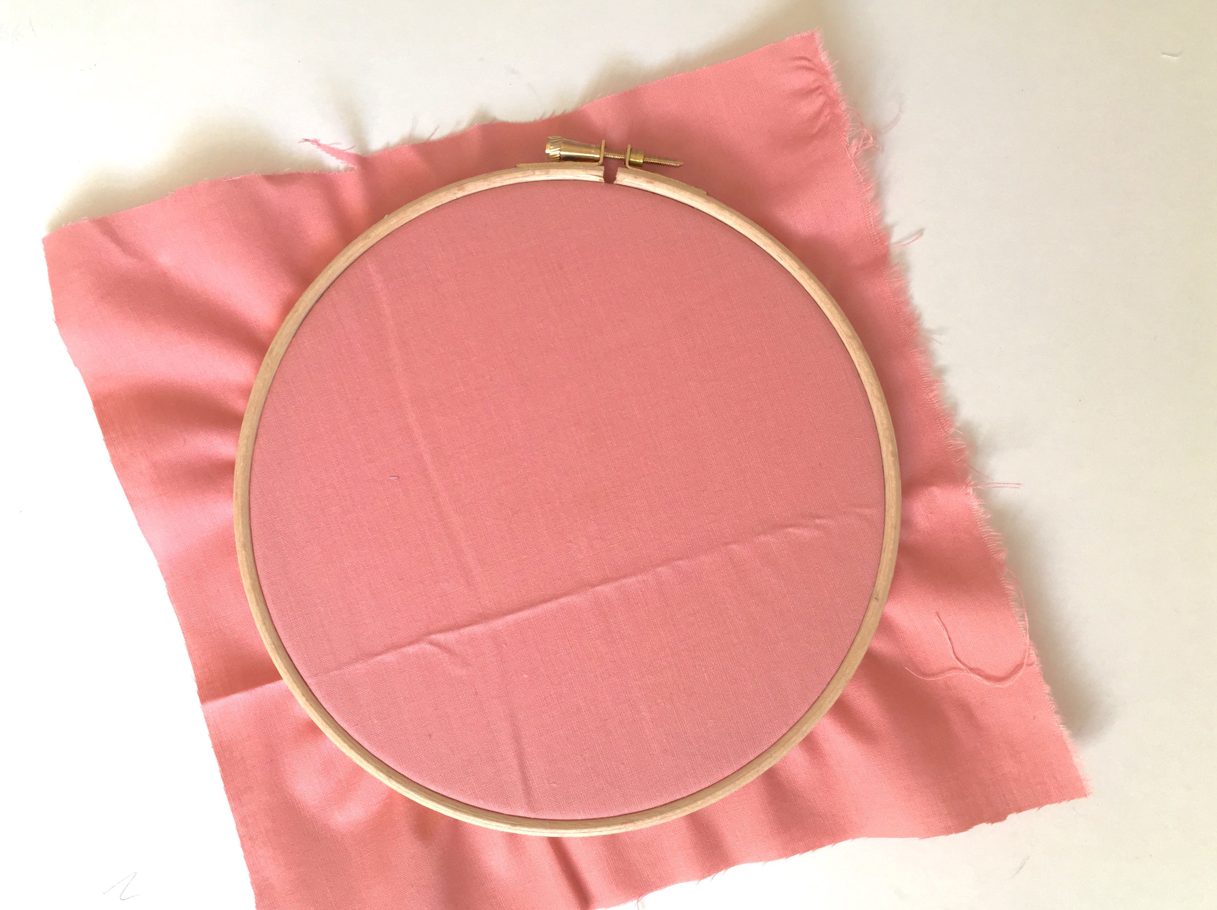 to fix your background fabric in place, loosen the screw at the top of your hoop. You don't need to unscrew it all the way. Once it's a bit looser you should be able to separate the inner and outer hoop. Place your fabric over the inner hoop, and then push the outer hoop over the top, so that the fabric is pinched in place between the two rings. Now you can tighten up the screw again to hold the fabric in place. -