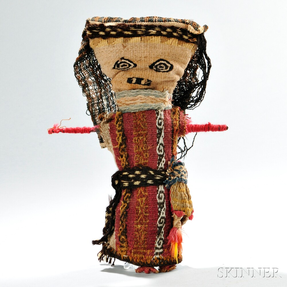 Chancay Textile Doll,  c. 1000-1400 AD, with woven facial features and carrying a coca bag with feather drops, Lucite stand, ht. 10 in. Via  Skinner Inc.