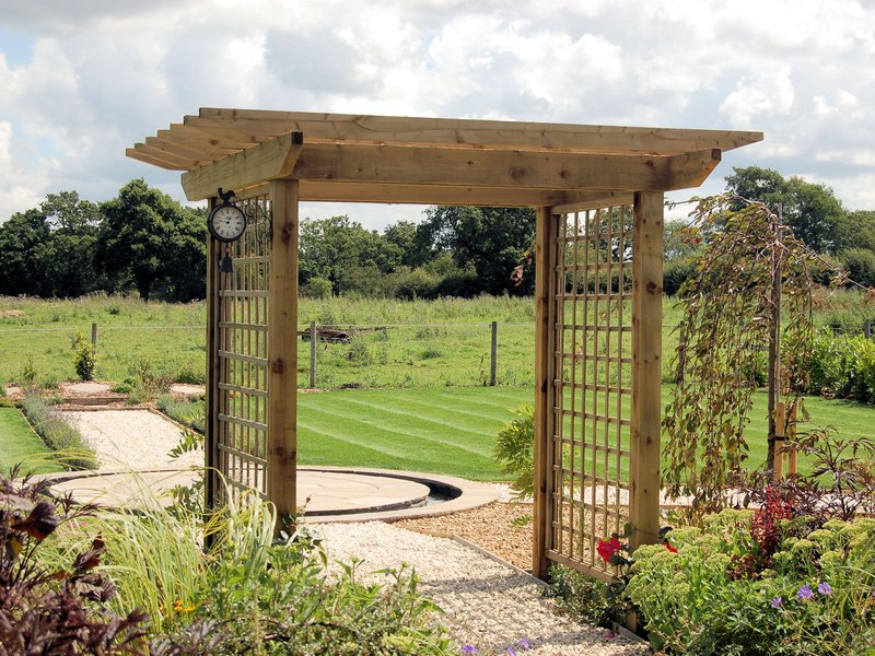 Bespoke arch built using our square trellis and timbers. Designed and built by Caddis Ltd