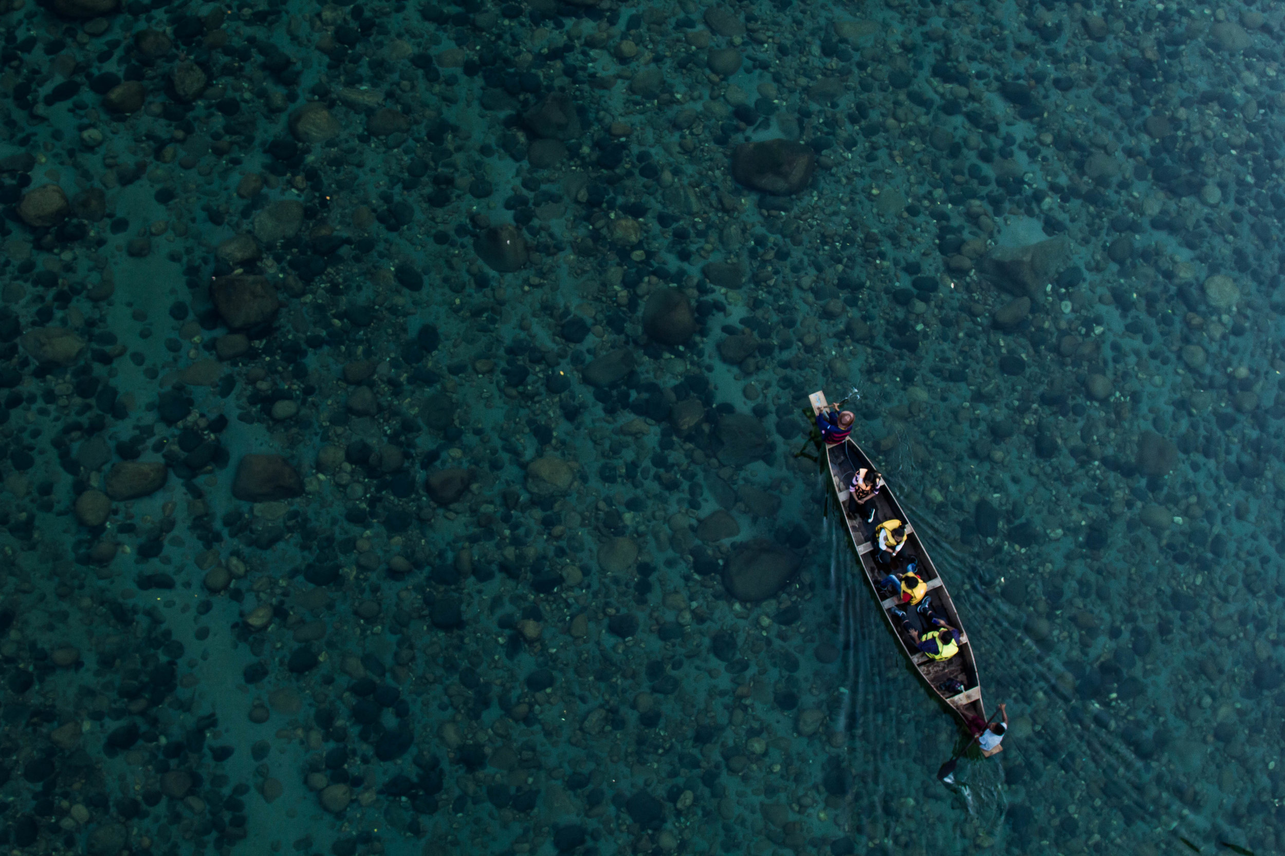 Overhead view of people rowing in a boat.