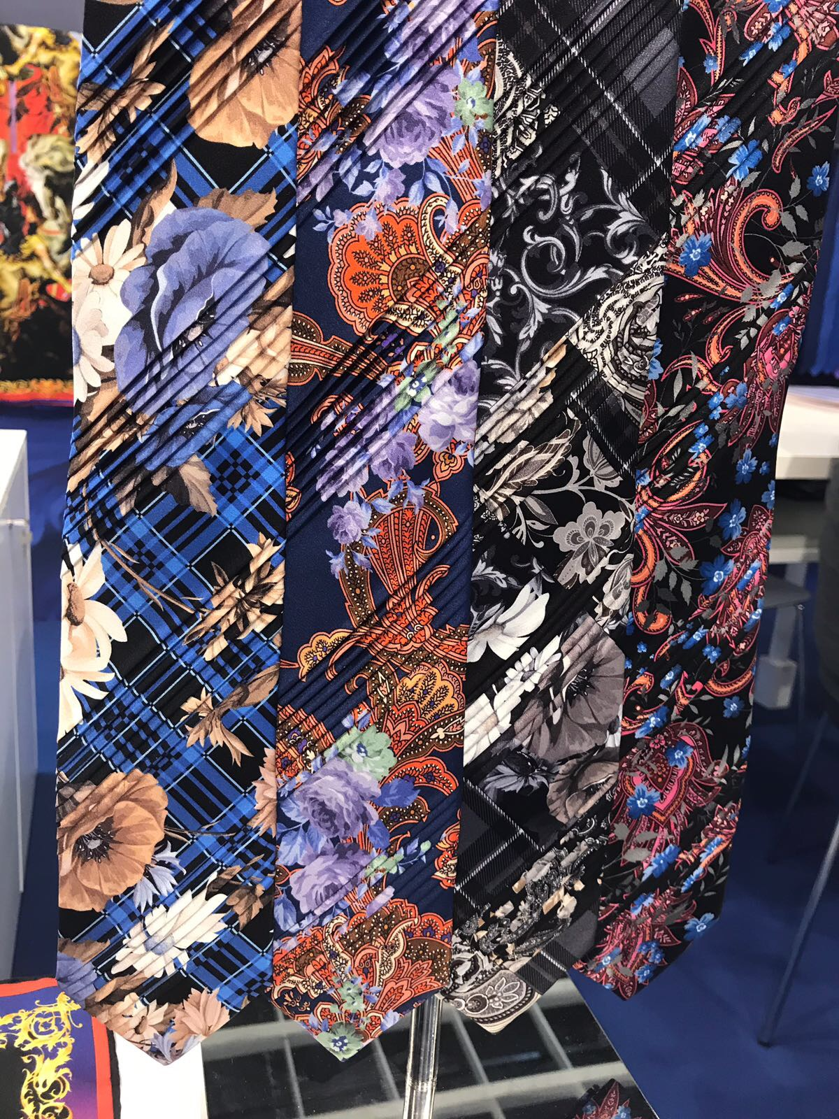 Pleated ties hanging on wall display.