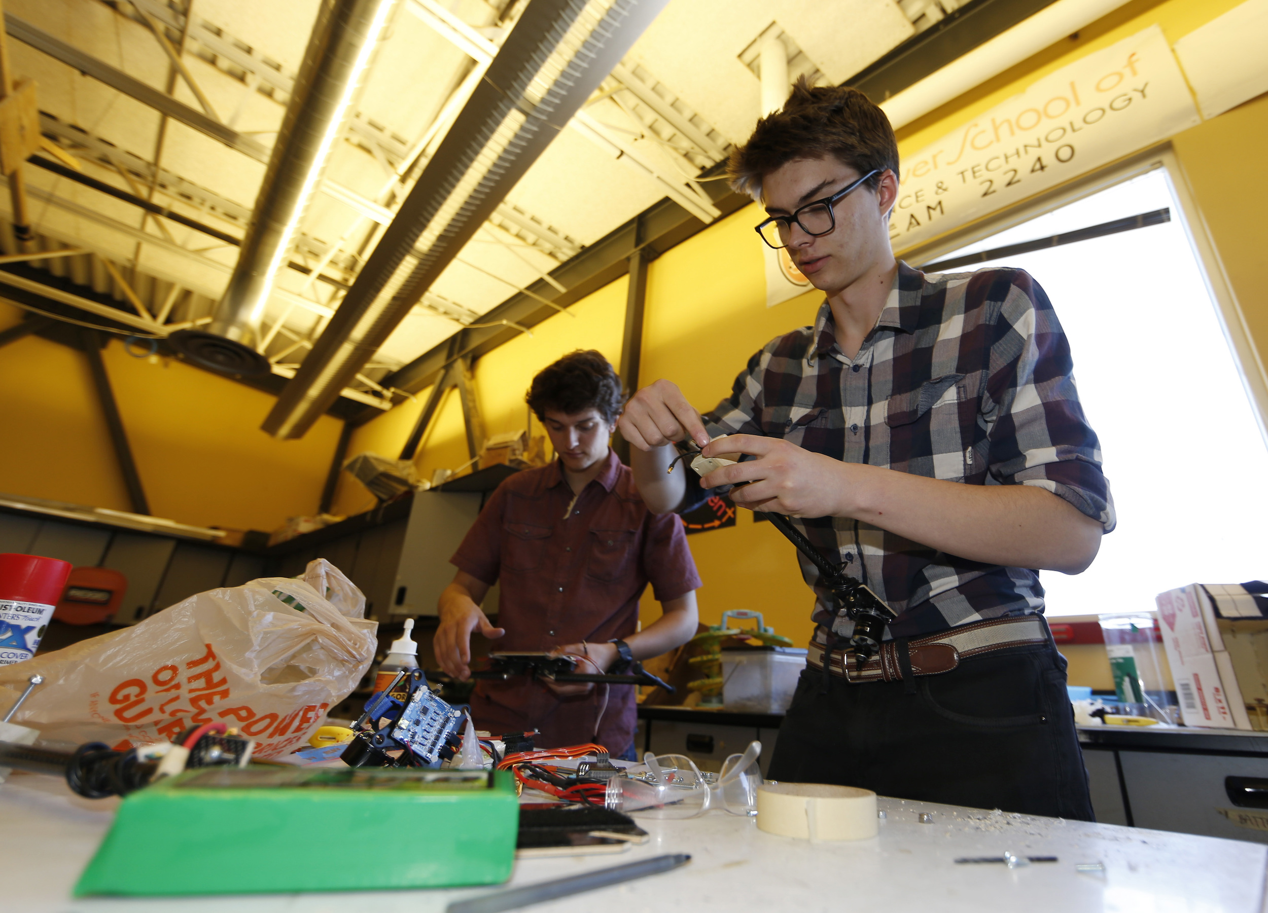 In this photo taken Friday, April 22, 2016, Nathan Lapore, right, and Max Alger-Meyer work on a drone at DSST Stapleton in Denver. Alger-Meyer, a Denver teen who visited Rwanda's Akagera National Park last summer, had an idea he thought would make the rangers' job easier: a drone. He and a friend have built one to donate to the park.