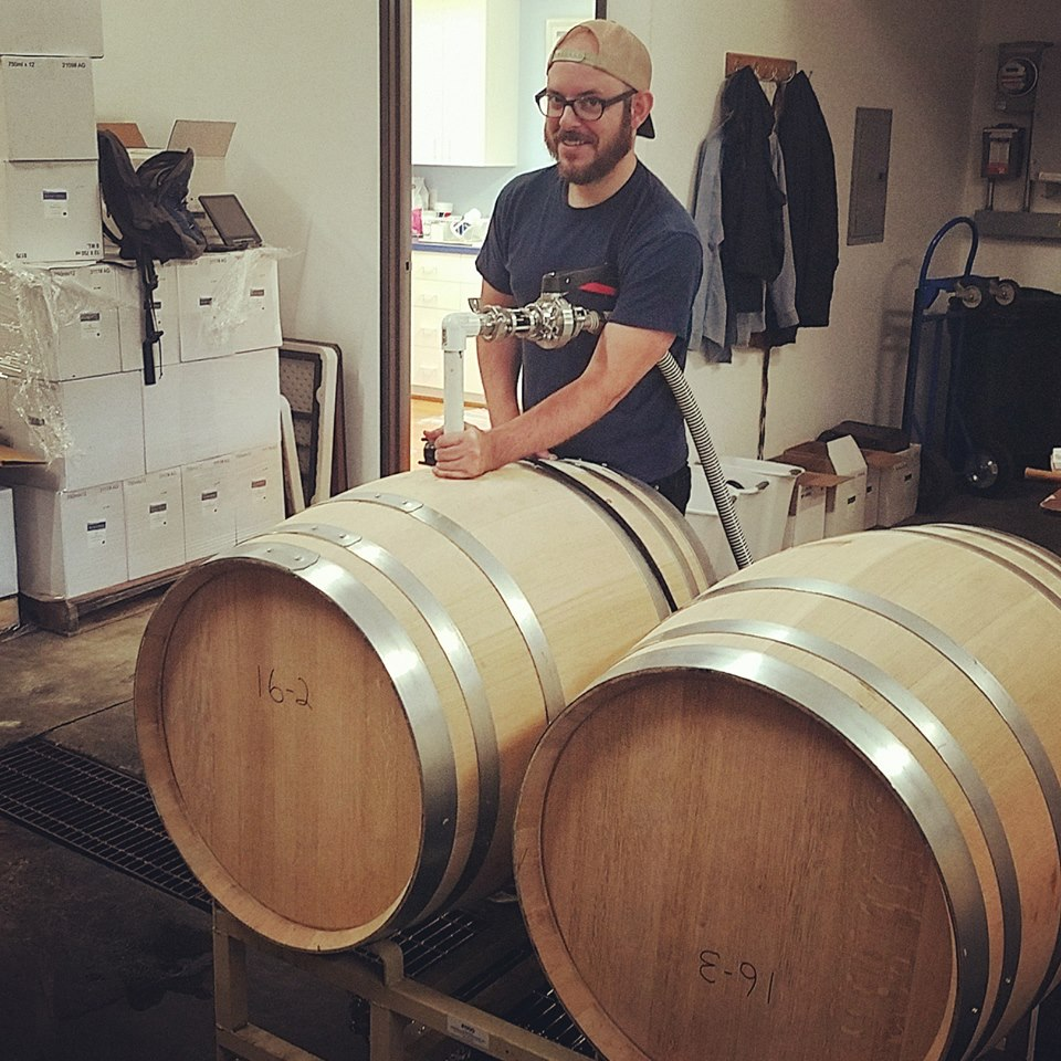 Colin Duddy posing while racking wine from an oak barrel