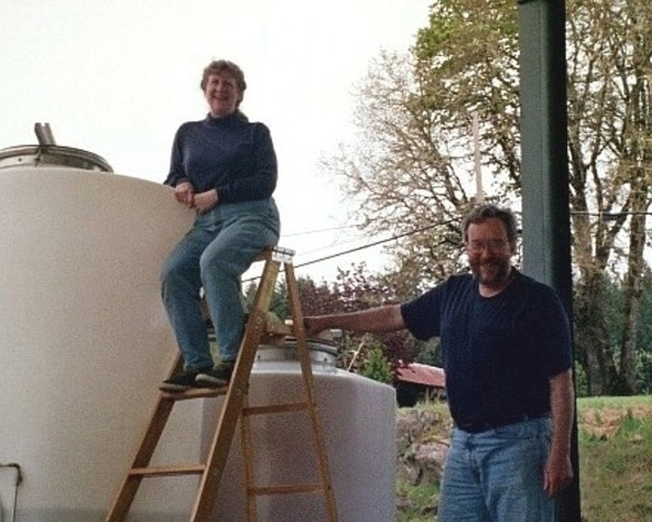 Mike and Vonnie Landt, posing in front of tanks used for winemaking.