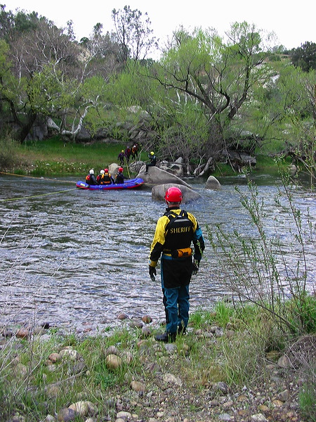 "Swiftwater Team - The Swiftwater Specialty Team are members who have achieved advanced training in water rescue. These members are very familiar and have a great deal of respect for the power of moving water. Much of the training in preparing for a water rescue is making sure the rescuer does not also become a victim. The rivers and creeks in our area become very different when it rains. The rivers and stream experience a huge increase in velocity and pick-up a great deal of debris. All the member of the swift-water rescue team have completed the Rescue 3 Swiftwater Rescue Technician and the team leaders have successfully completed the Rescue 3 Advanced Swiftwater classes. Special gear the teams use are Kokatat SAR Goretex dry suits, special life jackets for rescue work, rope guns for shooting a rope over the river, inflatable white water boats and some big ""boogie boards"" called Carlson boards."
