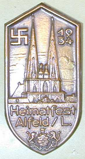 Heimetfest event badge 1934  with swastika, cathedral and Alfeld city arms A die struck gilded brass pin with a soldered spring pin (An examaple of mixing Church and State) (Source:  Snyder's Treasures, militaria collectables)