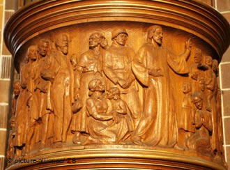 Wooden frieze carved into the side of the pulpit depicting Jesus standing next to a Nazi soldier and Aryan women and children.