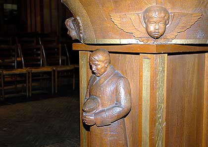 Baptismal front with carving of Hitler holding an stormtrooper hat.