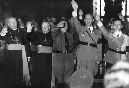 Catholic Bishops giving the Nazi salute in honor of Hitler. Note Joseph Goebbels (far right) and Wilhelm Frick (second from right)  (Source:  USHMM , Photo source:  Bayerische Staatsbibliothek  [Bavarian State Library])
