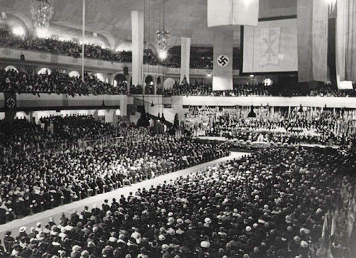 Welcome Celebration for Bishop Konrad Graf von Preysing in the  Sportpalast , Berlin, 8 Sept. 1935   Note the Catholic Chi-Rho Cross to the right of the Nazi flag. Chi and Rho are the first two letters of the Greek word for Christ. The Chi Rho Cross, or warrior's cross, originated from the monogram of Roman Emperor Constantine. How fitting it appears next to a swastika.  Following the death of Berlin's Bishop Bares, Pope Pius XI unexpectedly selects Konrad Graf von Preysing, a little-known Eichstatt bishop, as bishop of Berlin. Berlin, the region for which he is responsible, now also includes the center of the National Socialist power structure and so requires a high degree of political skill from its ecclesiastical leader.  (Photo source:  Gedenkstätte Deutscher Widerstand )