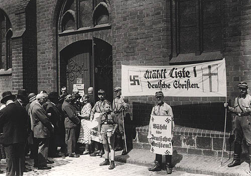 """Deutsche Christen (German Christians)   SA storm troopers with placards of the """"German Christians,"""" Berlin, July 1933.  On July 14, 1933, Hitler's government approves a new charter for the Protestant church. With massive intervention by the NSDAP, the church elections scheduled only a short time later result in a resounding victory for the """"German Christians."""" Hitler himself appeals to all Protestant Christians in a radio speech on the eve of the election to vote for the """"German Christians."""" With its slogan """"church must remain church,""""  (Source:  Gedenkstätte Deutscher Widerstand )"""
